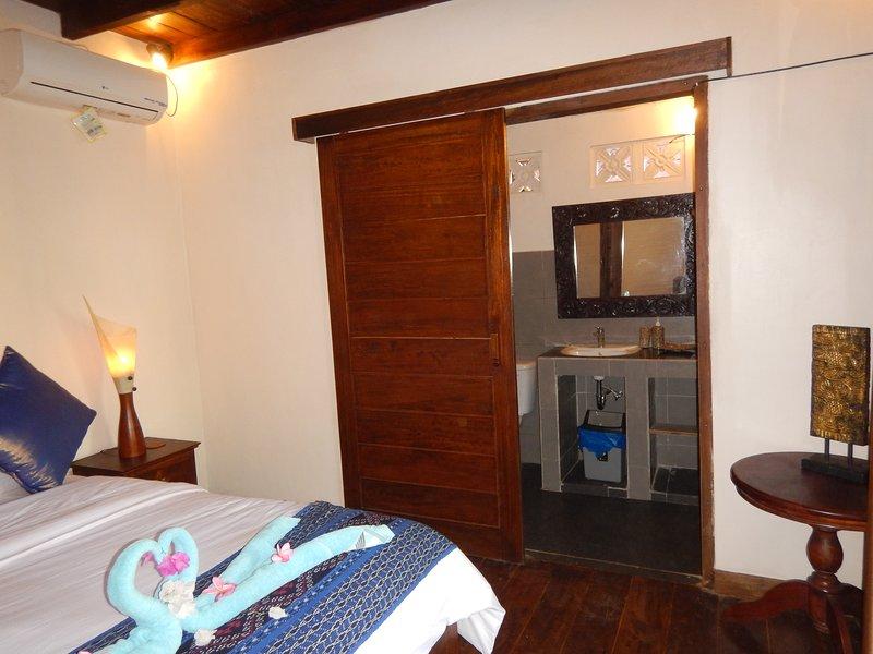 Puertas correderas de madera natural separa el baño del dormitorio.