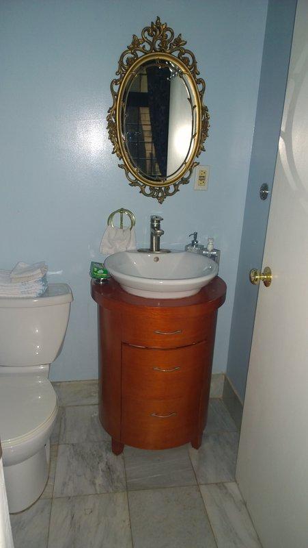Salle d'eau avec lavabo et WC. Sol en marbre.