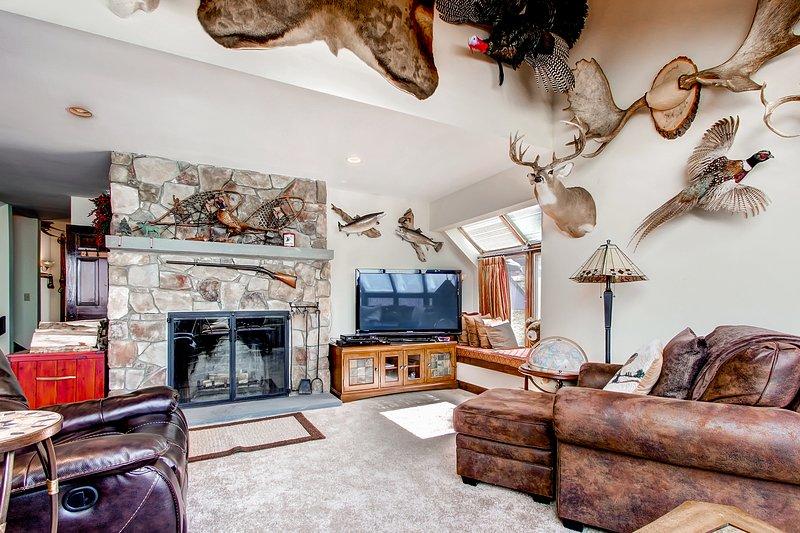A principal sala de estar e lareira com TV de tela plana e decoração rústica