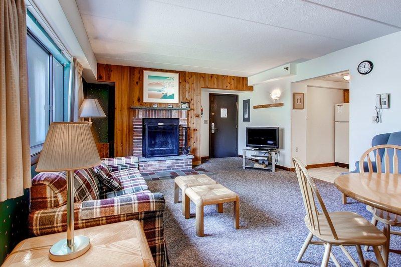 La sala de estar con un sofá cama, chimenea y TV de pantalla plana