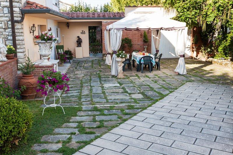 jardín al aire libre con cenador y apartamento entrada