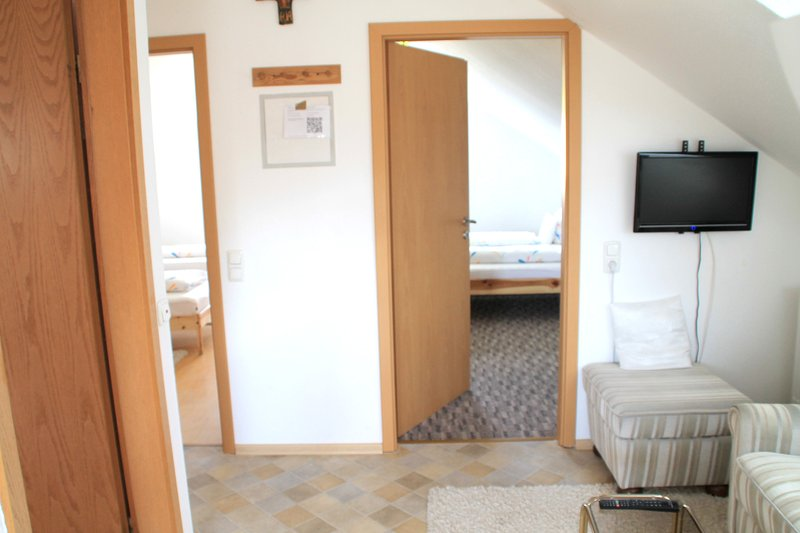 Hall with TV and 2 bedrooms