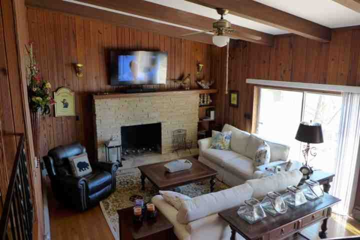 Living Room with New, Large, Flat-Screen TV's, Wood Beamed Ceiling, with Ceiling Fan.