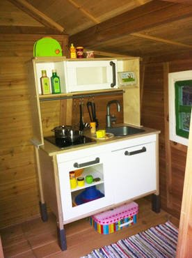 Children's playhouse lovingly decorated for children with bench and kitchen