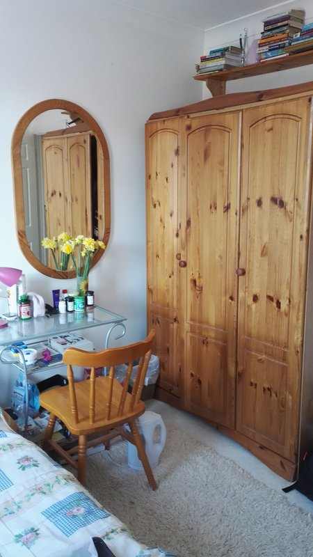 One side of the room, showing triple wardrobe, storage shelf, mirror, desk and chair