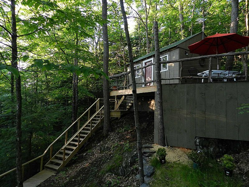 The cabin- built on posts, deck built into trees.