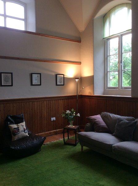Enormes ventanas en la habitación de la vieja escuela, permiten una gran cantidad de luz de inundación de la sala de estar
