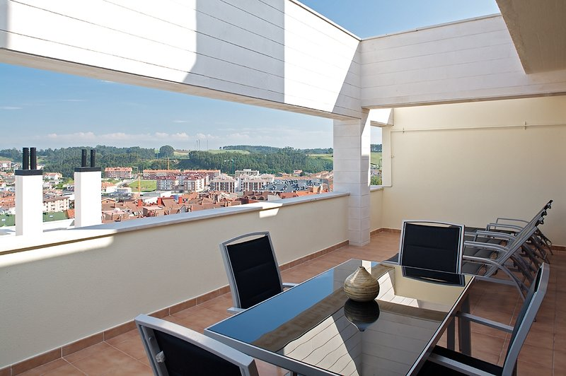 Large terrace, overlooking the sea, to Luanco, and with hammocks, outdoor furniture and dining table.
