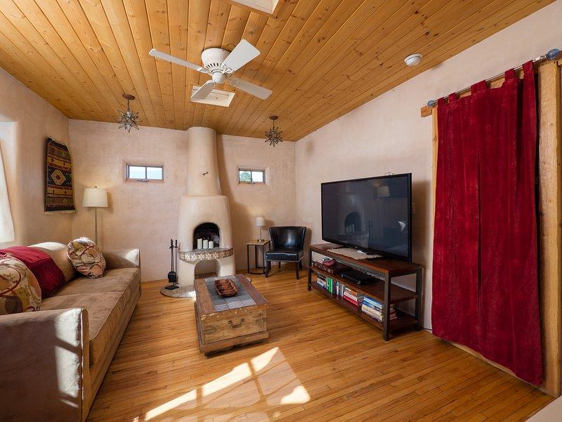 Vista completa de la sala de estar con sofá cama, chimenea kiva y TV