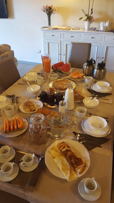 Breakfast with fruit, yogurt, cereals, jams, homemade cakes, omelets and toast