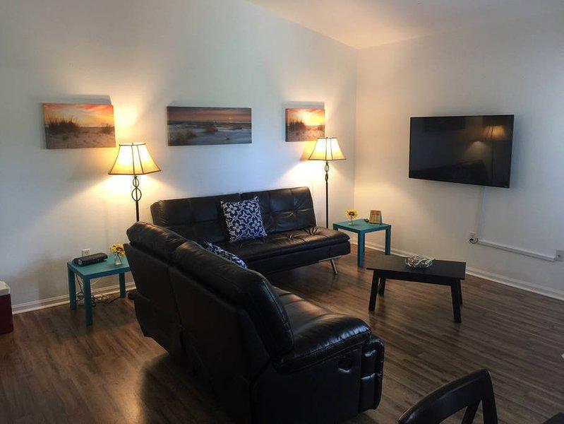 Vardagsrum med utdragbar soffa, två-sits fåtöljer, 55 tums HD Smart TV