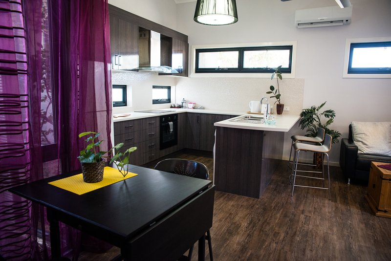 Fully equiped full sized kitchen with breakfast bench and dining table.