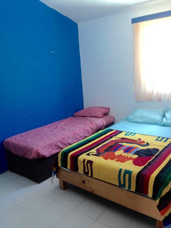 dormitorio de invitados con doble y dos camas individuales