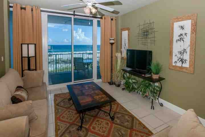 Tiled living room with flat screen TV/DVD and balcony access overlooking beach and Gulf