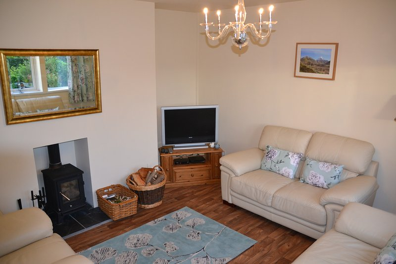 Living room with ample seating, log burner and sat tv