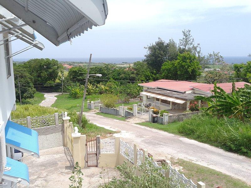 Detta är en ofullständig bild av det gröna landskapet och Karibiska havet sett från privat veranda