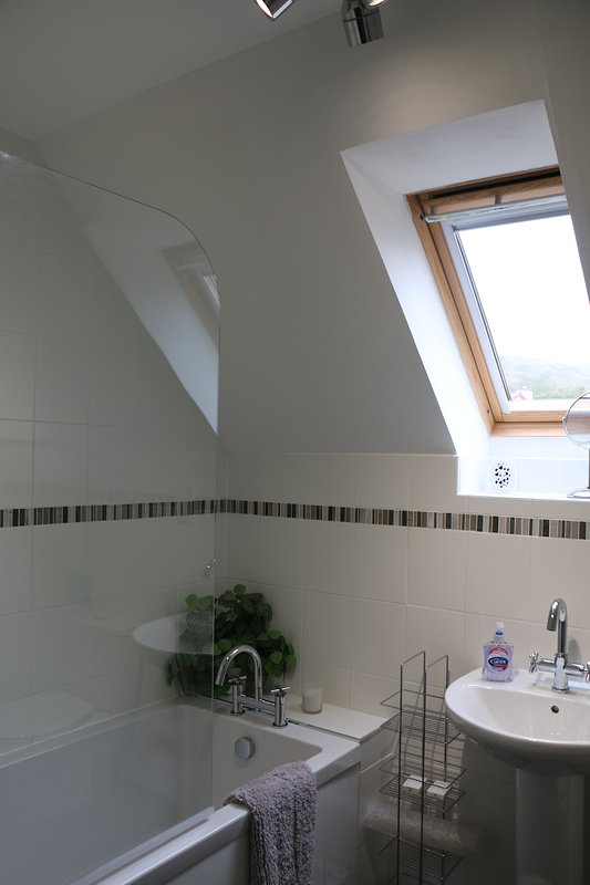 Spacious main bathroom with white suite, shower over bath.
