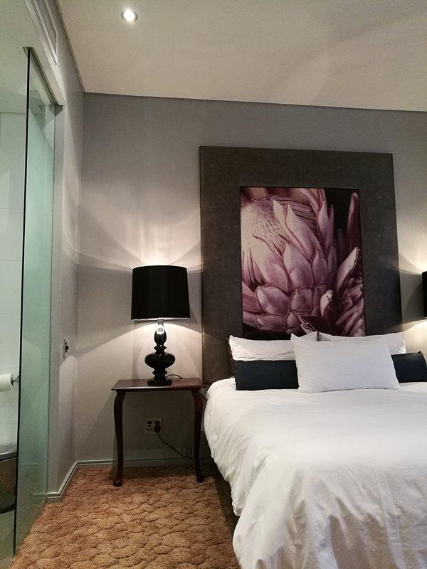 dormitorio principal con baño en suite accesible a través de puertas de cristal