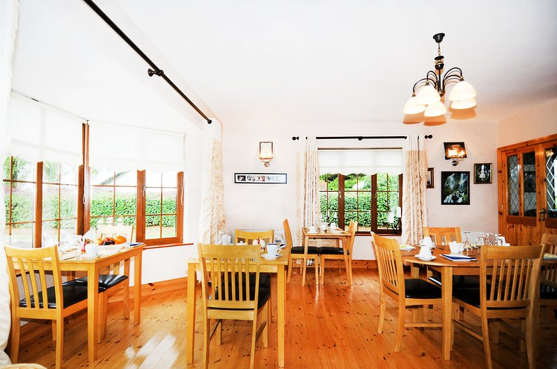 Wide angle overview of dining area. Spacious with plenty of natural light from large picture windows