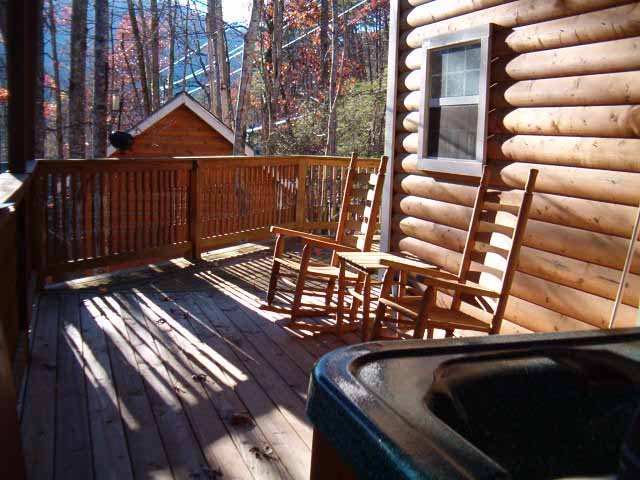 Rocking chairs HOT TUB under covered back porch. The small bldg. is storage on porperty