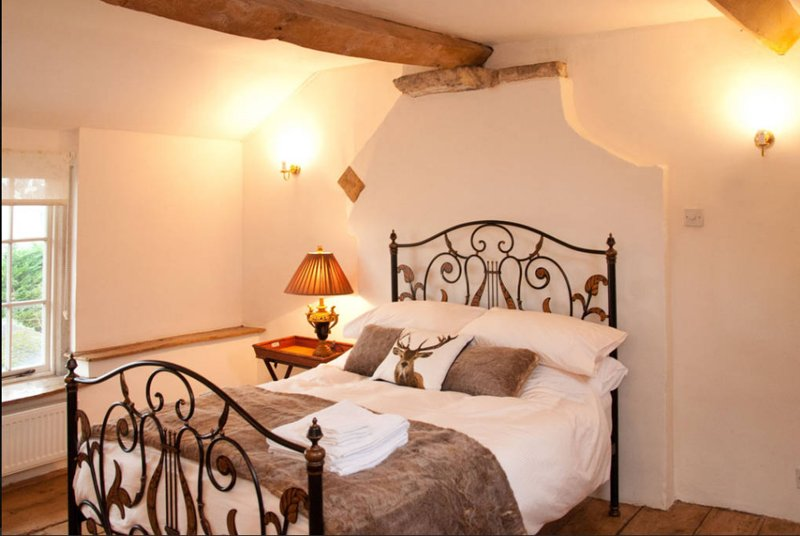 A light and airy double bed with exposed beam and original oak flooring