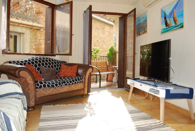 Salle de séjour avec télé HD et accès au balcon