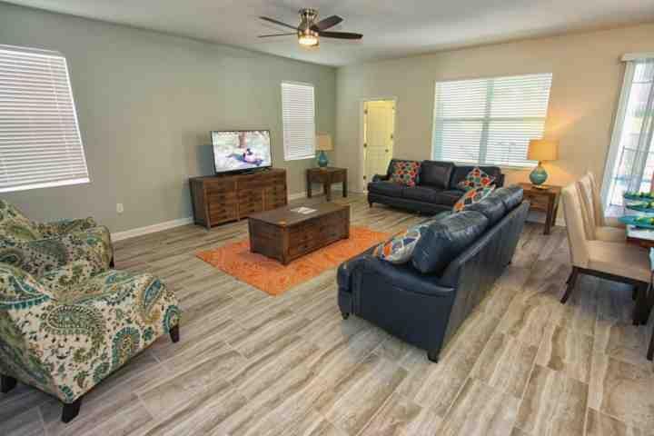 Área de estar elegante com assentos de couro, TV de tela plana e acesso à piscina