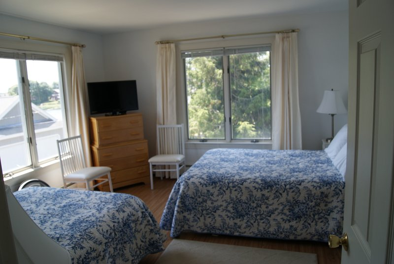 Third bedroom with two double beds. This view looks toward trees, garden, and street.