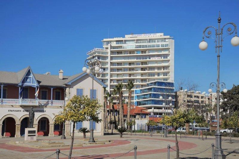 El exterior del edificio de apartamentos como se ve desde el paseo marítimo de Finikoudes y de la playa.