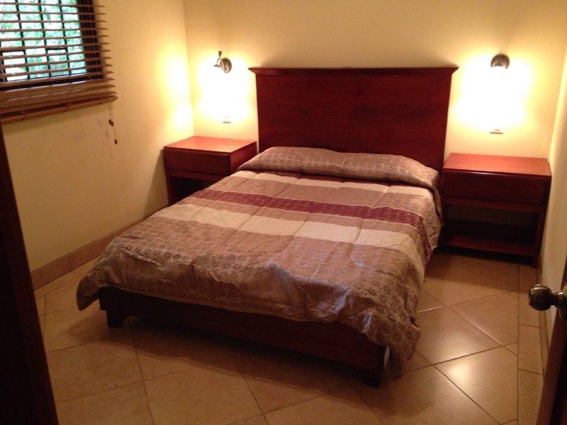 cama doble, 2 mesitas de noche con luces de lectura, y la percha de ropa con cajones