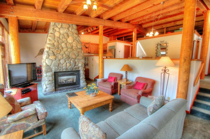 SkyRun Property - '2036 Homestead' - Living Room  - Recessed living room with floor to ceiling fireplace and exposed lodgepole pine timber cathedral ceilings.