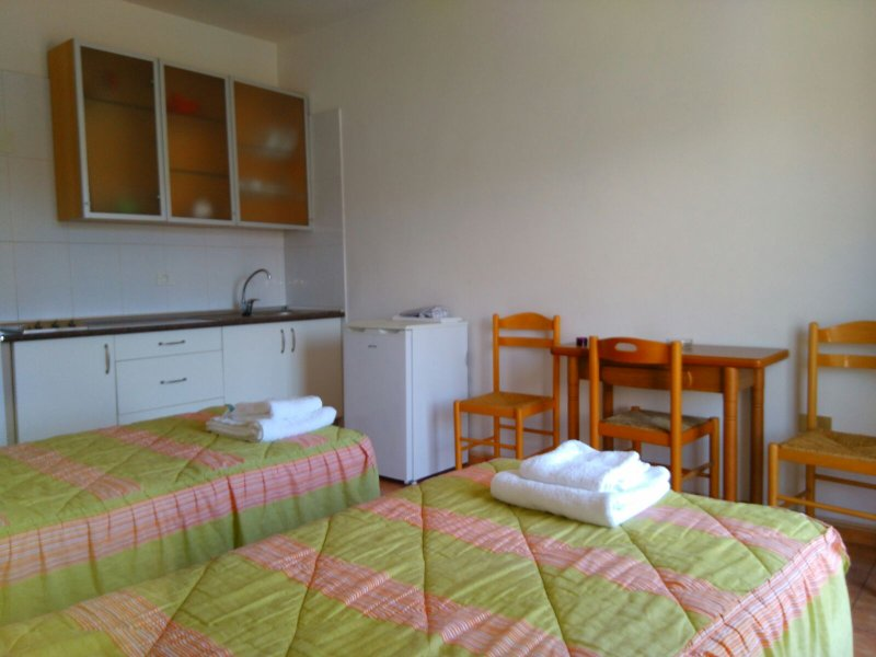 Studio avec deux lits simples et cuisine.