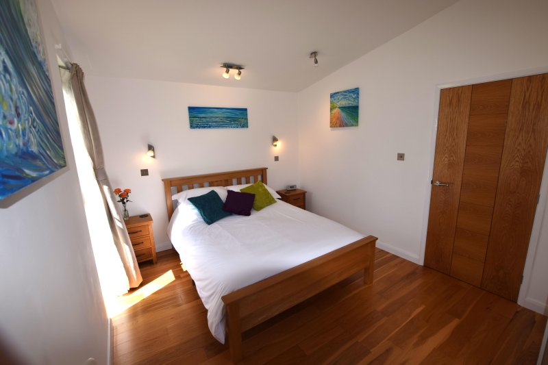 Spacious,comfortable bedroom has wardrobe and dressing table. Decorated with Pete Caswell art work.