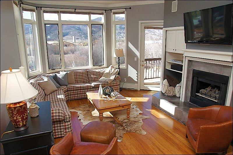 Wohnzimmer verfügt über hohe Decken, Gas-Kamin und Holzböden