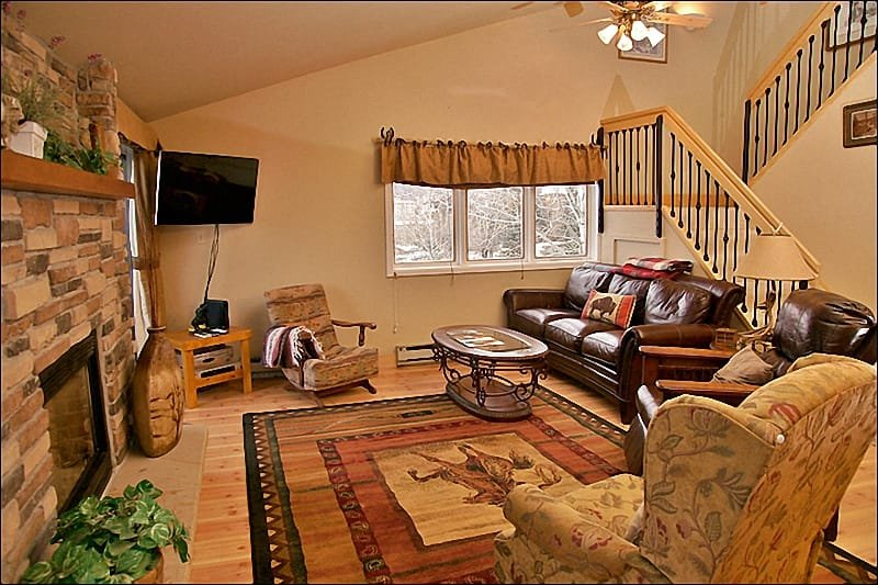 Beautiful Living Room features Leather Furniture, Fireplace, Hardwood Floors, TV, DVD, & Balcony with Gas Grill!
