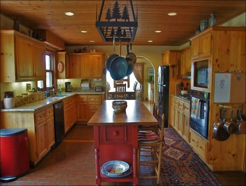 A very open Kitchen with Granite Counters, Gas Range & Butcher Block Island.
