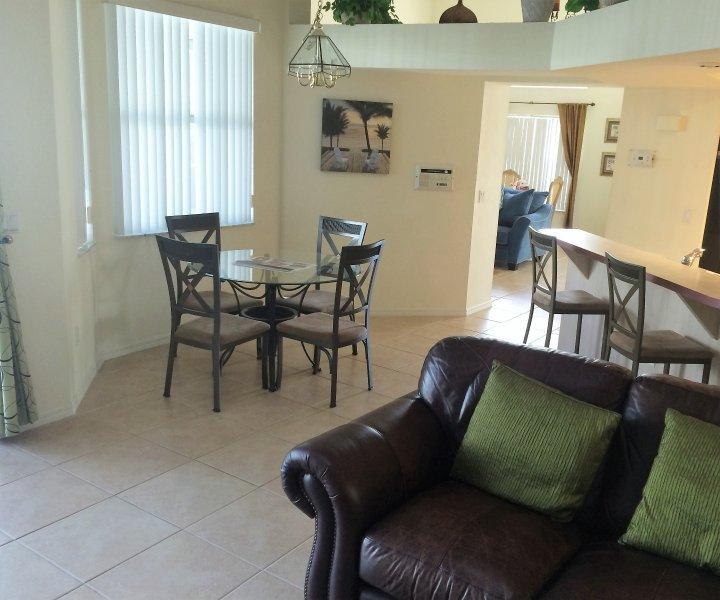Vanuit familiekamer terug te kijken op de keuken eettafel met uitzicht op het zwembad en een deel van het ontbijt bar