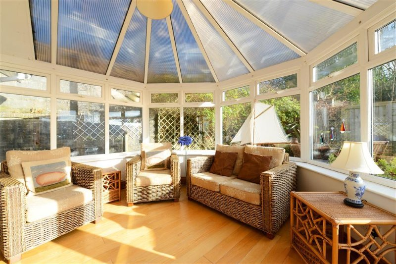 Sunny Conservatory looking out on to decking, bbq and coastal views beyond