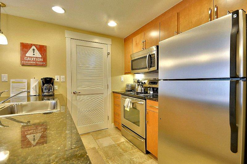 Groot formaat koelkast, oven, kookplaat en roestvrijstalen apparaten