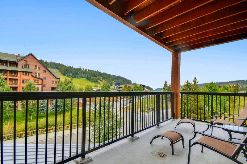 Overdekt terras met uitzicht op de bergen en stoelen met poef