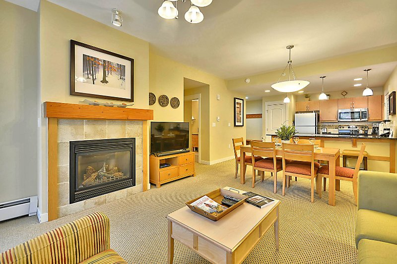 Living Room with Fireplace and 55' Smart TV, Dining Table and Full Kitchen