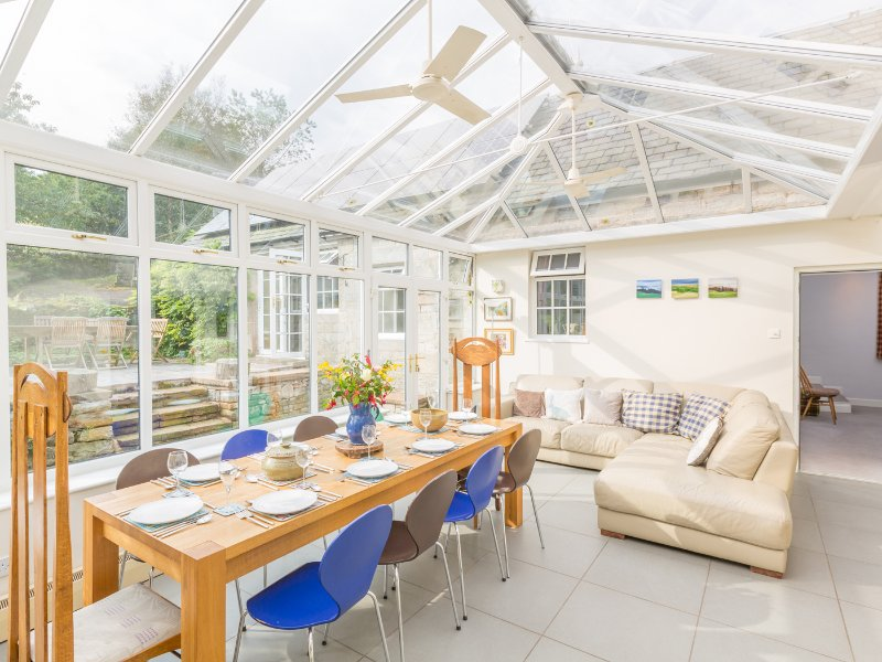 Conservatory with large oak dining table for 10 and a very comfy sofa.
