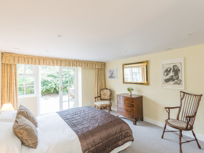Large bedroom with king size bed, French doors and walk-in wardrobe.