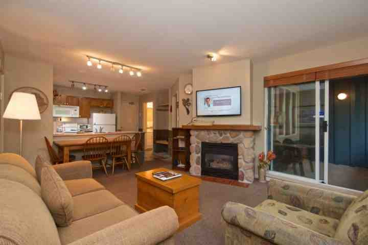 Spacious living room with gas fireplace and wall mounted TV