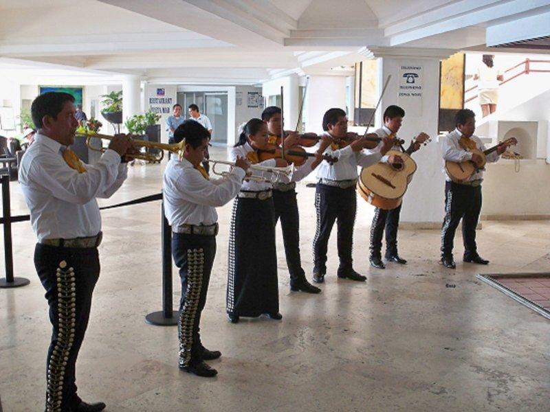 Mariachi band serenades personeel en gasten in de grote lobby.