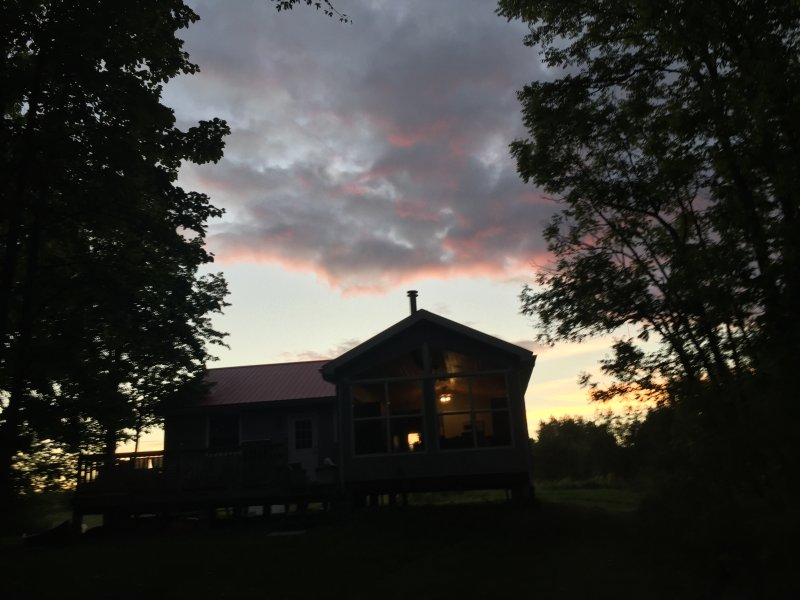 View of the cottage at night coming in from the lake.