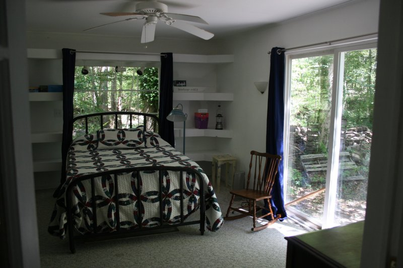 Main level, Blue Bedroom, has double bed and sliding glass door to outside.
