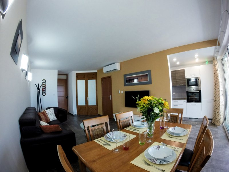 Living/dining space with recessed kitchen flooded with natural light overlooking the balcony