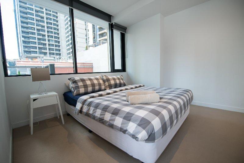 Une chambre avec un lit queen et des oreillers moelleux.