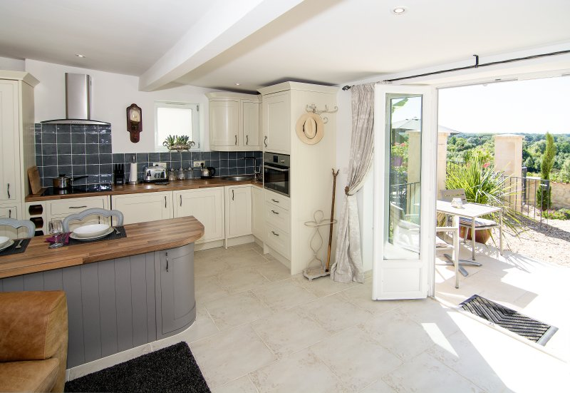 The sunny kitchen area leads out onto a private patio with stunning panoramic views
